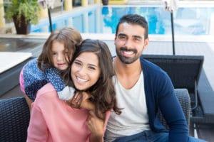 family smiling beside pool