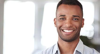 man in grey shirt smiling